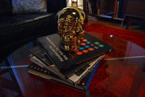 The ever changing stack of coffee table books guarded by our golden skull. (That book on the top is one of my favorites, I am such a Geek!)