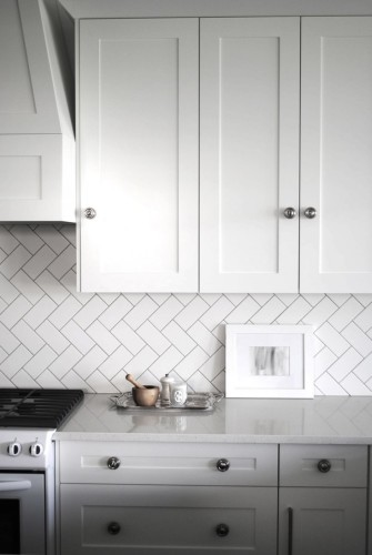 There is too much white going on here, but the herringbone tile on the wall is absolutely amazing... This can be done with inexpensive 3x6 inch white subway tile you can pick up for a quarter a piece at the big box store (if you don't mind glossy tiles).