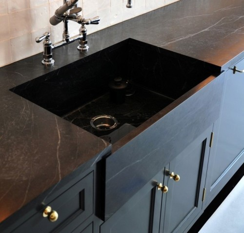 Soapstone counters.... Love them! In fact I love this whole set up with the dark cabinets and brass hardware.
