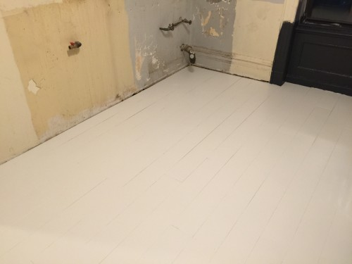 Once the damaged floor was repaired, we put down a temporary floor consisting of 1/4 inch plywood planks painted in white porch paint. The plan was to for it to last five years until we were ready to do our dream kitchen... Plans change.