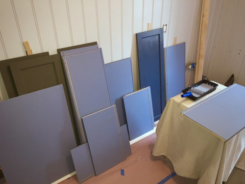 Painting the insides and outsides of the dozens and dozens of cabinet components. Here are mostly the insides of the upper cabinets drying along the wall.