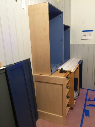 Five of the eight cabinets for the sink wall are shown completed to the point of being ready to install. On the left is two of the side panels in Stiffkey Blue.