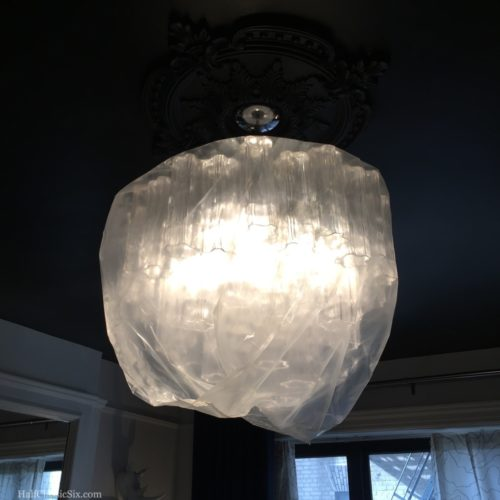We wrapped our chandelier in a giant plastic bag to keep the dust at bay. Fortunately, the LED bulbs don't generate enough heat to be concerned about the plastic.