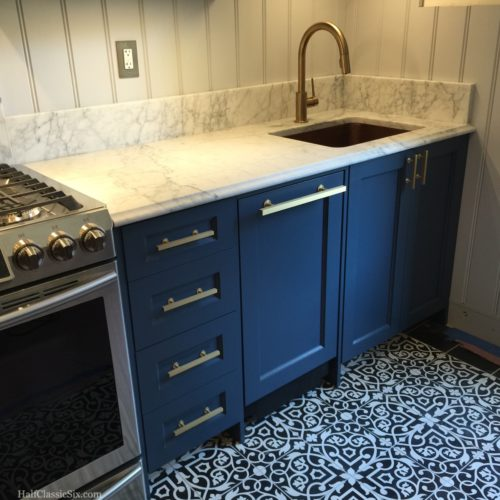 I am completely in love with how everything complements each other. The Stiffkey Blue cabinets, black and white cement tile floor, honed Carrara counters, beadboard walls, and brass hardware.